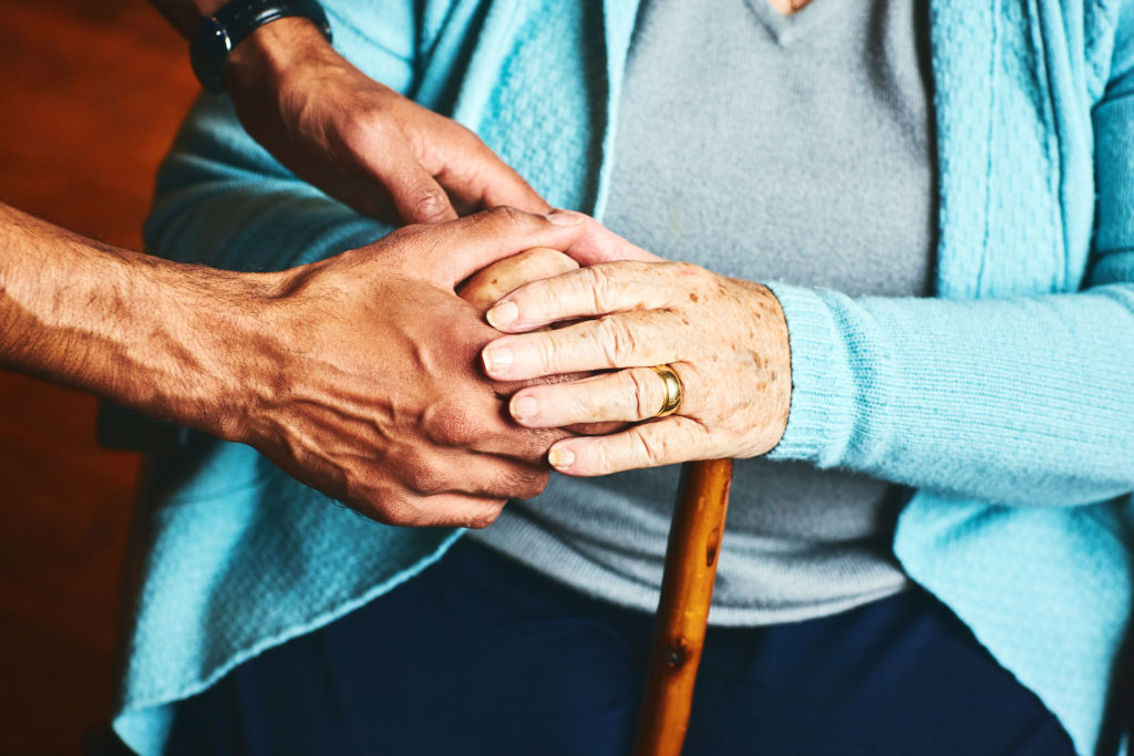 Close up of male carer holding hands of senior woman, home caregiver showing support for elderly patient.